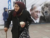 Пожилая женщина на фоне плаката с Владимиром Путиным в Санкт-Петербурге