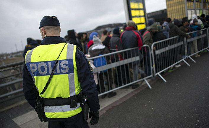 Полицейский следит за мигрантами в Швеции