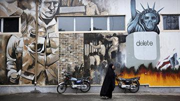 Женщина на фоне граффити на стенах бывшего посольства США в Тегеране, Иран