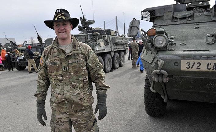 Капитан американской армии возле боевой бронированной машины «Страйкер»