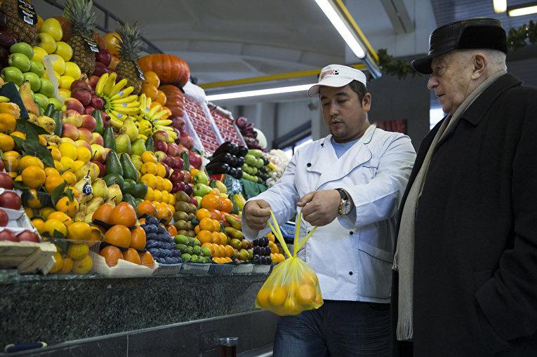 Мужчина покупает мандарины на рынке в Москве