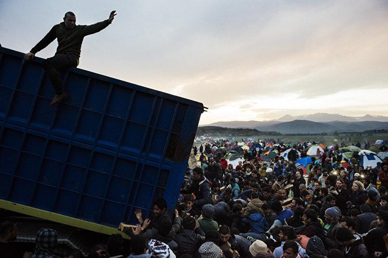 Беженцы запасаются дровами во временном лагере на границе Греции и Македонии