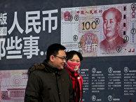 Стенд с информацией о новой купюре в 100 юаней на улице в Пекине