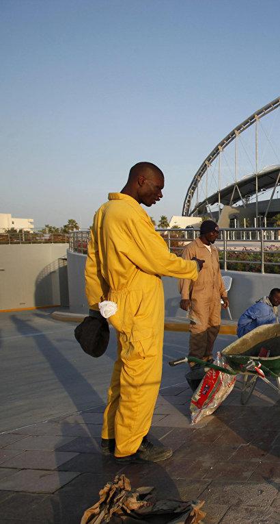 Рабочие рядом со стадионом «Халифа» в Дохе