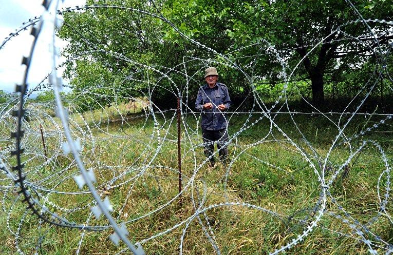 Местный житель возле колючей проволоки на границе Грузии и Южной Осетии