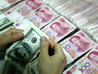 Банковский служащий пересчитывает доллары рядом с пачками юаней в городе Хуайбэй, Китай