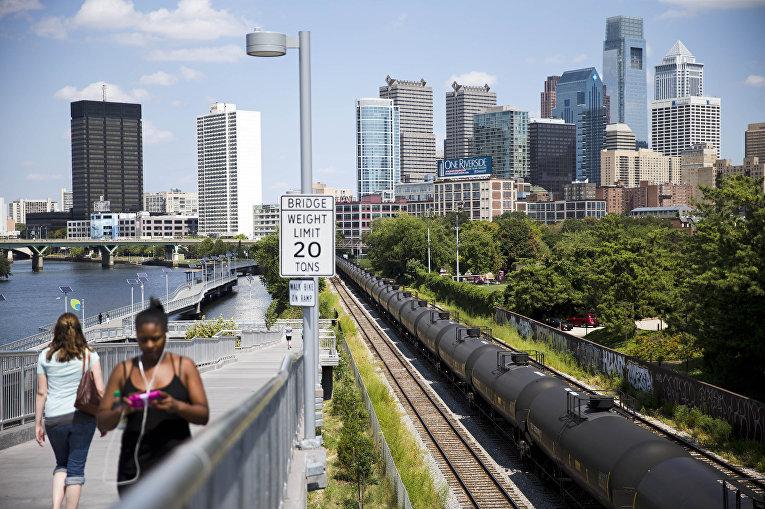 Люди проходят мимо цистерн с сырой нефтью в Филадельфии