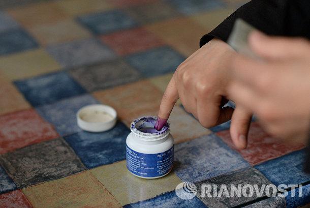 Женщина опускает палец в емкость с чернилами для отметки в списке избирателей во время голосования на парламентских выборов в Сирии