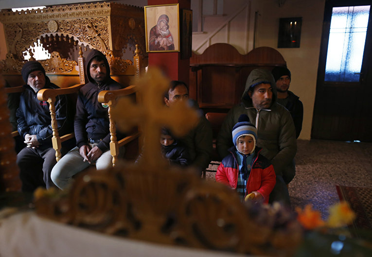 Сирийские беженцы-католики на службе в православной церкви в деревне Идомени, Греция