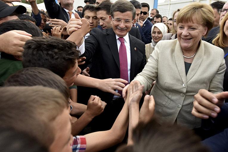 Премьер-министр Турции Ахмет Давутоглу и канцлер Германии Ангела Меркель встречают беженцев