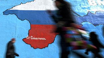 Прохожие у нарисованной на стене карты Крыма в цветах российского флага в Москве