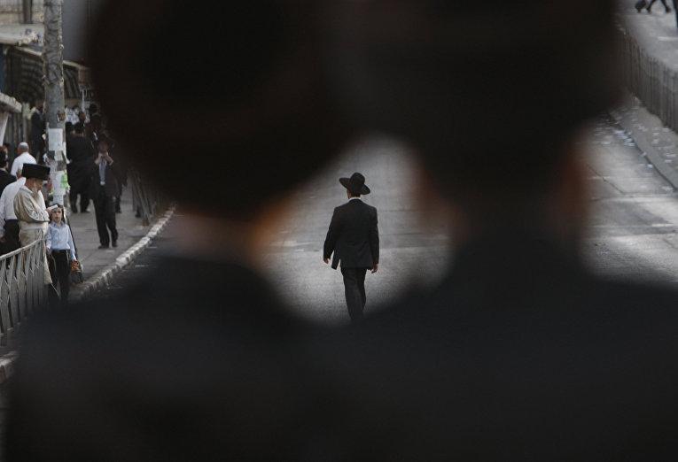Ультраортодоксальный еврей идет по пустой улице в Иерусалиме