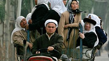 Уйгуры едут на тракторе на базар в Кашгаре