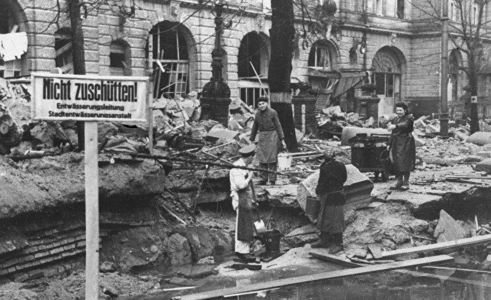 Берлинцы набирают воду на улице полуразрушенного города, апрель 1945 года