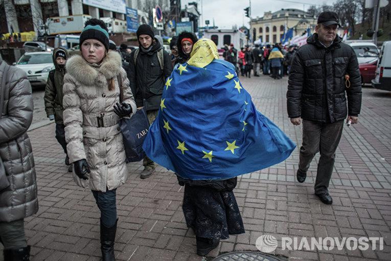Женщина, обернувшаяся во флаг ЕС, идет по Крещатику в Киеве.