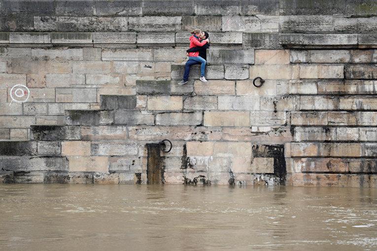 Парочка на берегу реки Сена в Париже