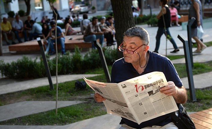 Мужчина читает газету на проспекте Баграмяна в Ереване