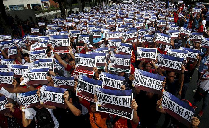 """Активисты держать плакаты с надписью """"Руки прочь от Филлипин!"""" во время акции протеста по спорам в Южно-Китайском море"""