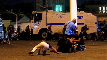 Люди прячутся от стрельбы на площади Таксим в Стамбуле. 16 июля 2016