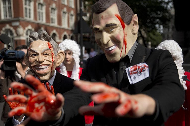 Демонстранты в масках бывшего премьер-министра Великобритании Тони Блэра и экс-президента США Джорджа Буша