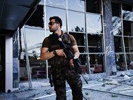 Сотрудник полиции возле разрушенной в результате попытки переворота штаб-квартиры полиции