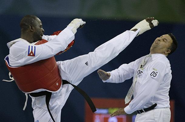 Анхель Матос наносит удар судье Чакиру Челбату после поражения в поединке с Арманом Чиламановым во время Олимпийских игр в Пекине