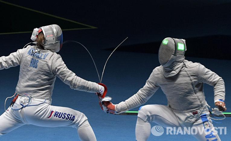 Николай Ковалев (Россия) и Альдо Монтано (Италия) в поединке соревнований по фехтованию на саблях на XXXI летних Олимпийских играх