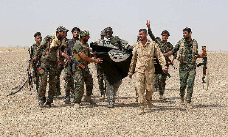 Бойцы иракских полувоенных формирований с сорванным в Нибаи флагом Исламского государства