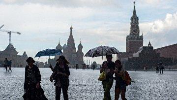 Горожане во время дождя на Красной площади в Москве