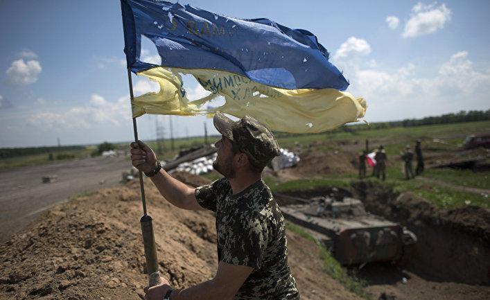 Украинский военный устанавливает флаг Украины в Марьинке недалеко от Донецка