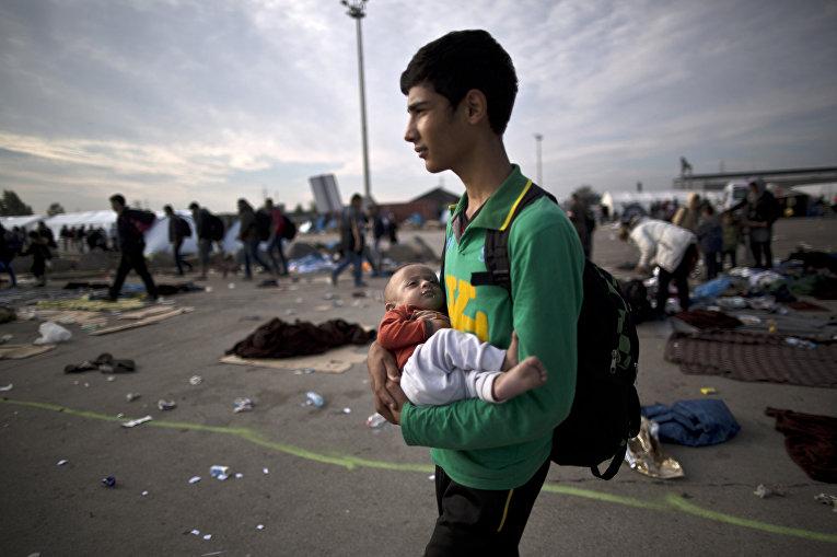 Беженец из Афганистна с 10-тимесячным племянником на руках после пересечения венгерско-австрийской границы