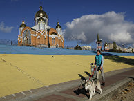 Девушка выгуливает собаку возле Покровского собора в Киеве