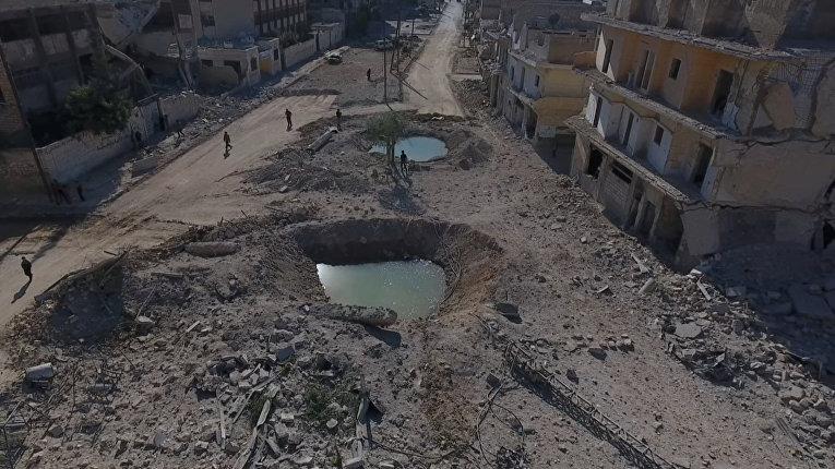 Воронки и разрушенные здания в районе, контролируемом повстанцами Алеппо