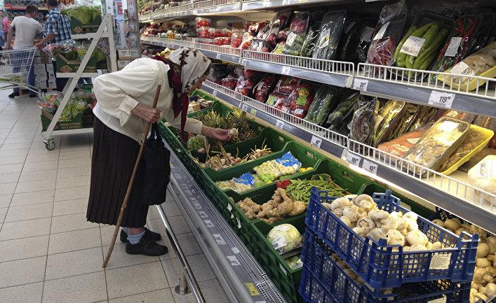 Пожилая женщина выбирает овощи в супермаркете в Дмитрове