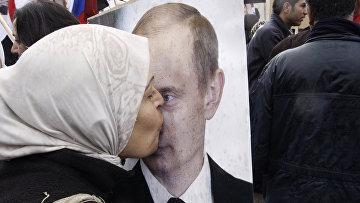 Сирийская женщина целует портрет президента РФ Владимира Путина