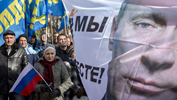 Плакат с изображением президента РФ Владимира Путина во время митинга в Симферополе
