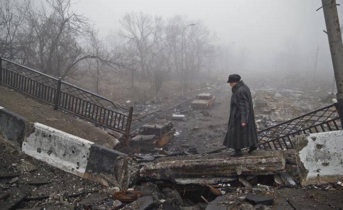 Женщина идет по полуразрушенному мосту в Донецке