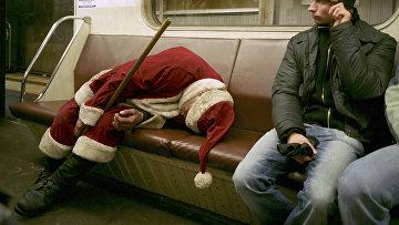 Выпивший человек, одетый Дедом Морозом спит в московском метро