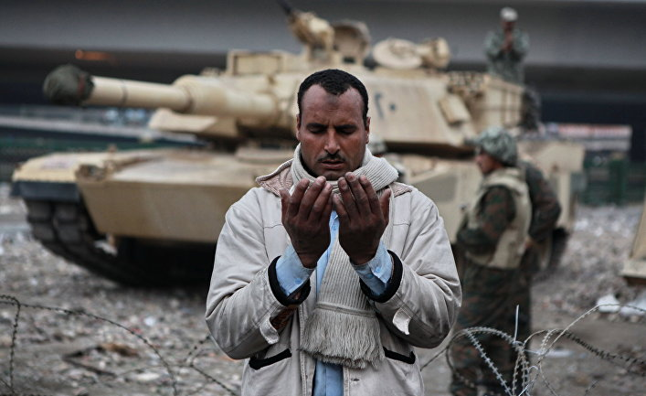 Сторонник оппозиции молится на площади Тахрир в Каире