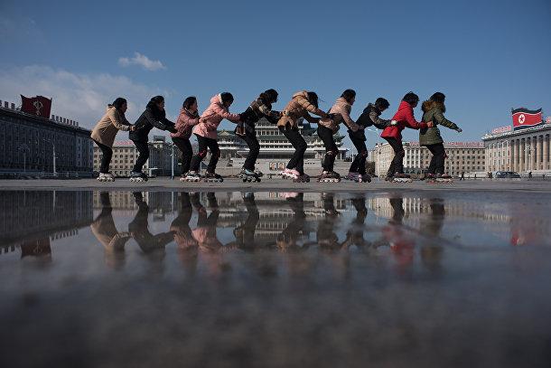 Группа детей на роликовых коньках на площади имени Ким Ир Сена