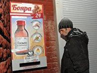 Мужчина у автомата по продаже спиртосодержащего средства с боярышником