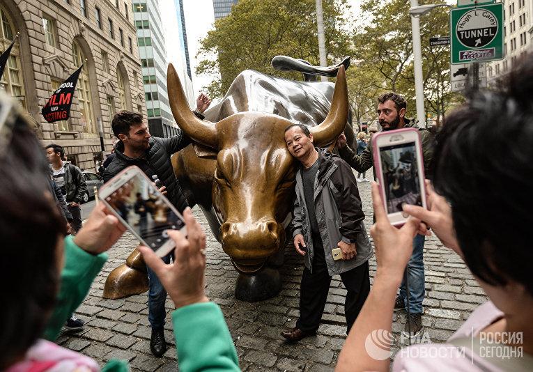 Туристы фотографируются у скульптуры «Атакующий бык»