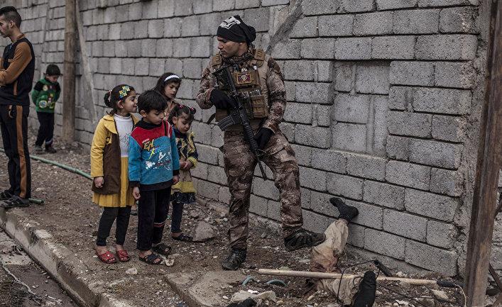 Дети рассматривают полузакопанный труп боевика ИГИЛ