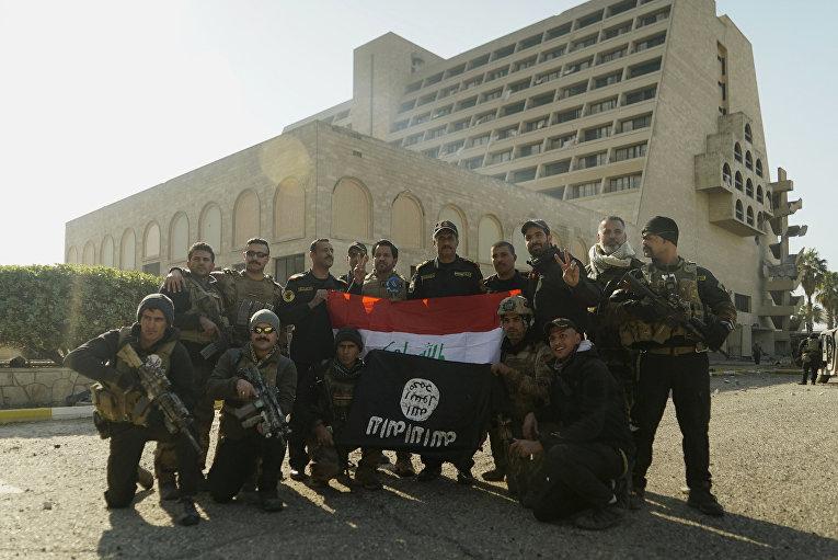 Иракские спецназовцы позируют с национальным флагом и захваченным боевиками ИГИЛ напротив гостиницы Nineveh