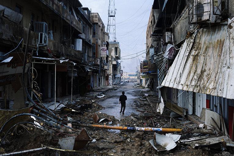 Иракский мальчик идет по разрушенному городу