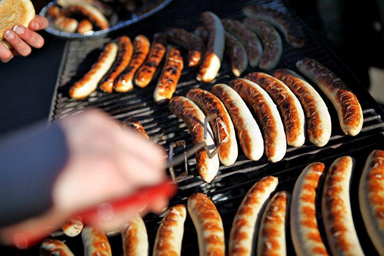 Женщина жарит сосиски в Германии