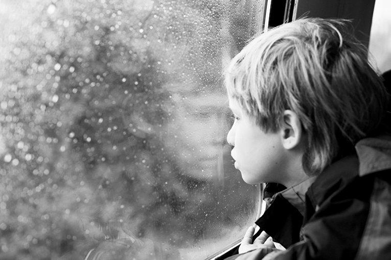 Мальчик смотрит в окно
