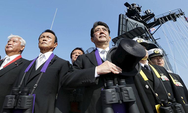 Премьер-министр Японии Синдзо Абэ, министр финансов Японии Таро Асо и министр обороны Гэн Накатани во время смотра флота в бухте Сагами