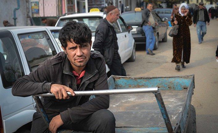 Грузчик на Зеленом рынке в городе Душанбе в Таджикистане