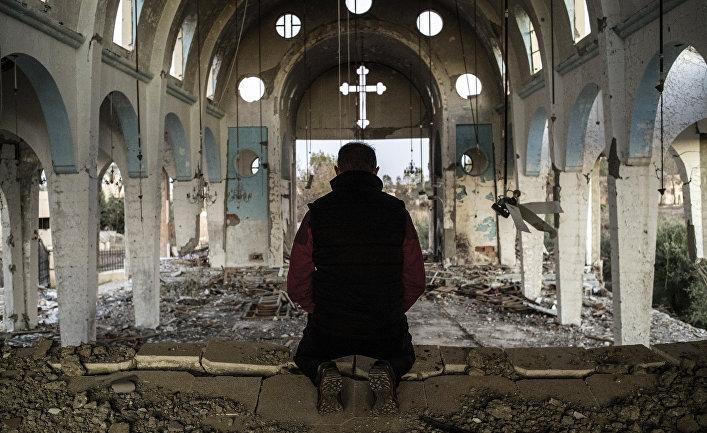 Житель одной из деревень в провинции Эль-Хасаке на северо-востоке Сирии молится в храме Святого Георгия, уничтоженного боевиками ИГ (организация запрещена в РФ)
